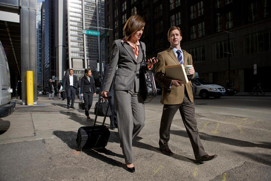 Business Colleagues Talk And Walk Down A Busy Chicago Street.