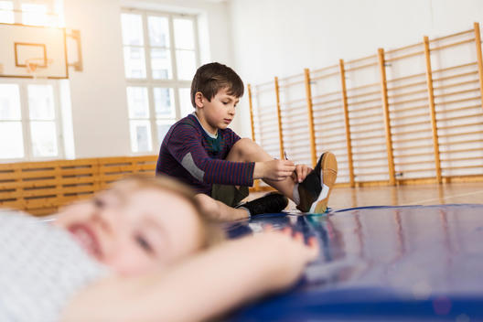 Children sitting on blue exercise mat, boy tying shoelace