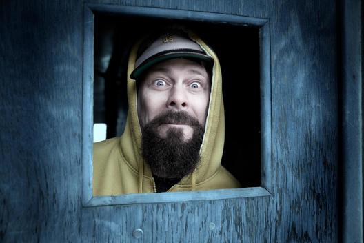Hooded and Bearded man in door window