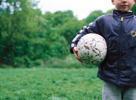 Boy standing with soccer ball under arm
