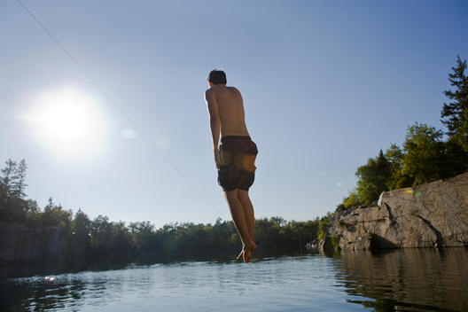 Young Man In Mid Air Jumping Into A Lake