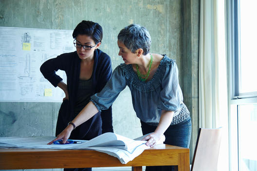 Two businesswomen studying blueprints in office