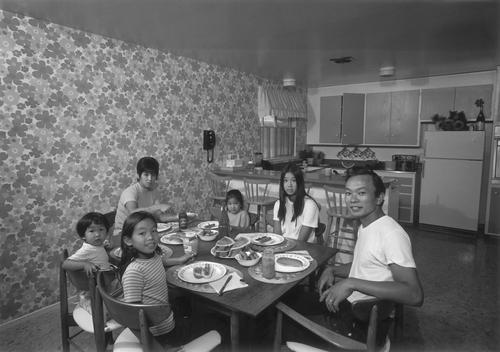 An Asian family eats a dinner of hotdogs