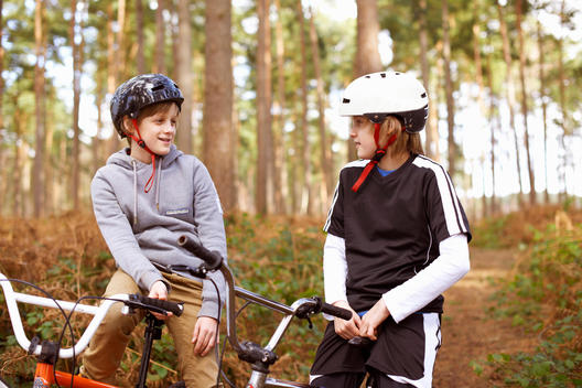 Twin brothers on BMX bikes chatting in forest