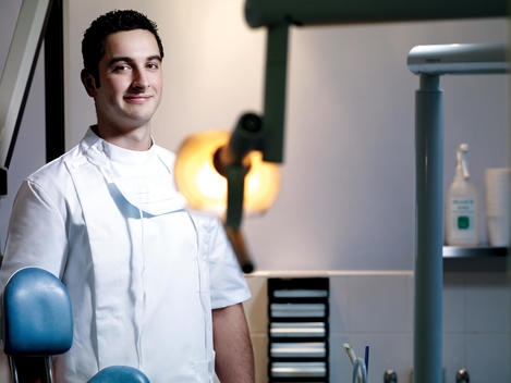 Young Male Dentist Standing Near Dental Treatment Equipment, Smiling Portrait