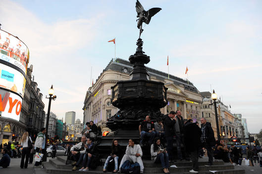 People are sitting around the Shaftesbury Memorial Fountain at Piccadilly Circus in London.