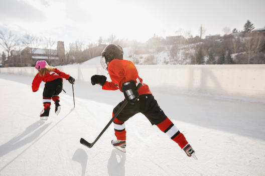 Ice hockey players skating on outdoor rink