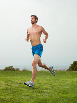 An athletic young man jogs on a grassy seaside cliff