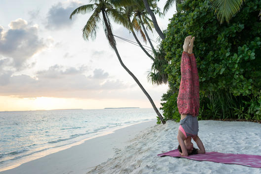 Woman doing yoga on beach in the Maldives.