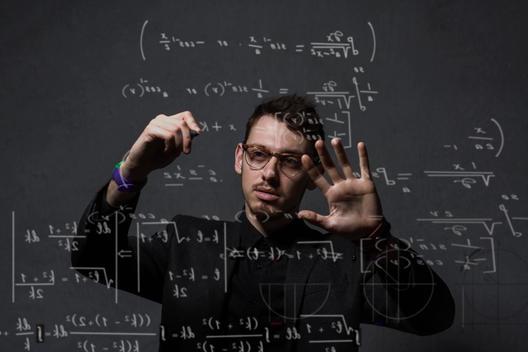 Man writing mathematical equations on glass wall