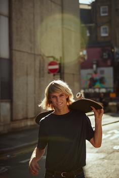 Man holding skateboard in street, sun flaring
