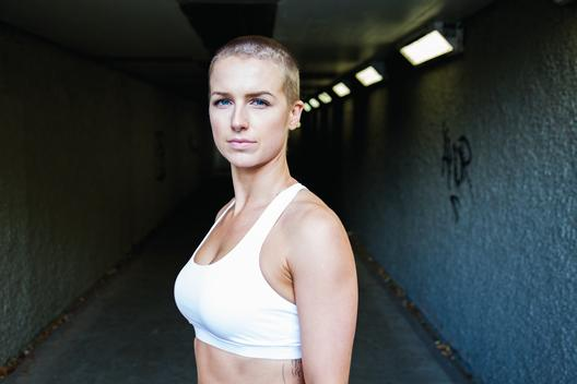 Portrait of woman wearing athletic attire, standing in city tunnel.