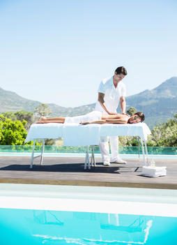 Woman receiving massage at poolside