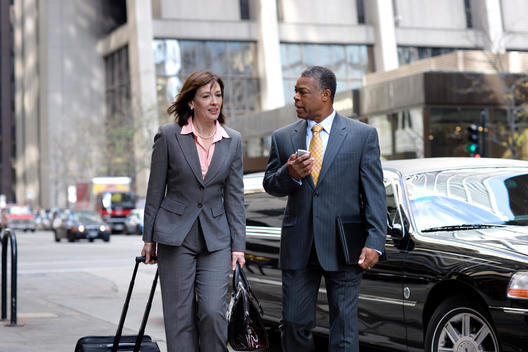 Two Business Colleagues Talk And Walk Together On A Chicago Street.
