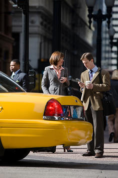 Business Colleagues Stand Near A Taxi On A Busy Chicago Street.
