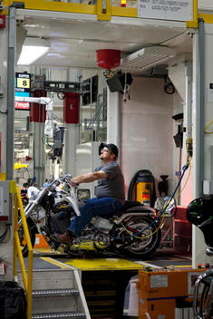 A male worker sits on a brand new motorcycle to test it inside the Harley Davidson factory
