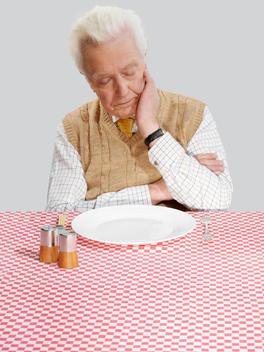 Senior Man Sleeping Whilst Waiting For Food