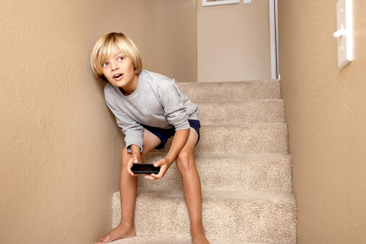 Boy (7-10 years old) glancing into the room from the staircase, holding game controller