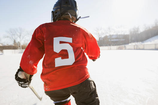 Rear view of ice hockey player skating on rink