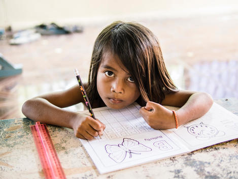 A girl does schoolwork at The Wat Opot Community, an orphanage for children affected by HIV and AIDS, near Chambak, Cambodia, outside Phnom Penh.