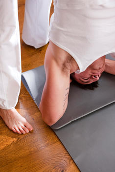 Yoga instructor helping man in the head-stand position - close up