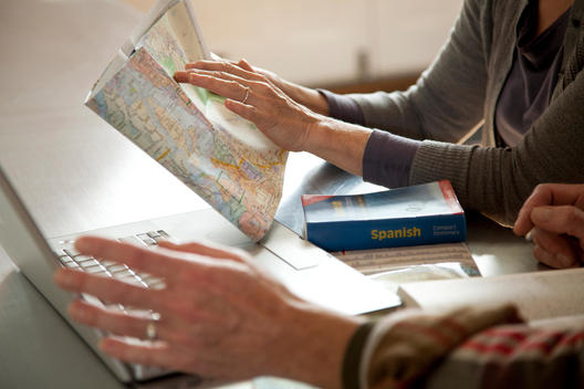 Older couple reading map and laptop
