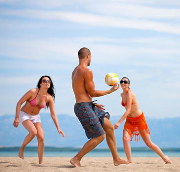 Croatia, Zadar, Friends playing volley ball at beach
