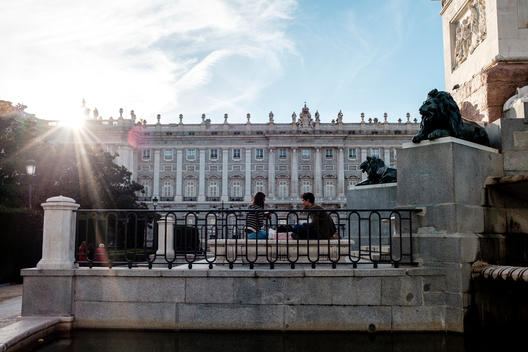 Tourists sit in front of the Royal Palace in Madrid, Spain.