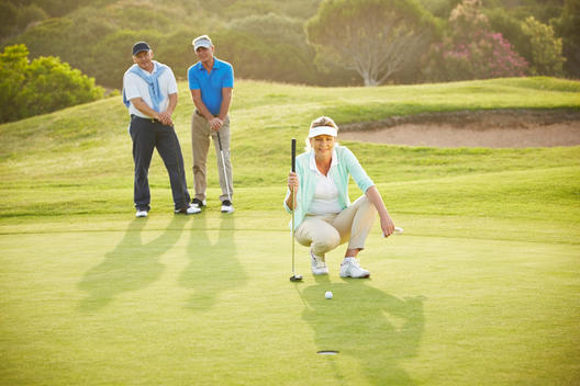 Senior friends playing golf on course