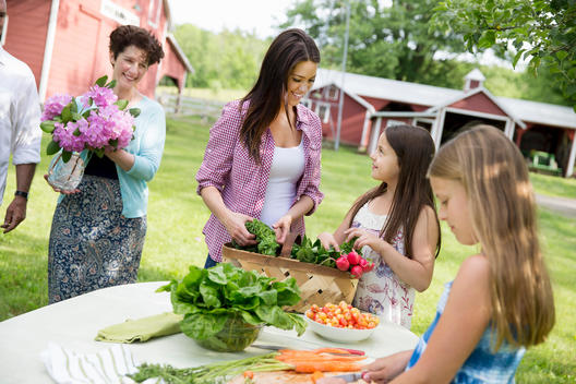 Family Party. Five People, Parents And Children Around A Table Preparing A Meal Of Fresh Picked Salads, Fruits And Vegetables Together.
