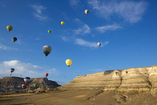 Large group of hot air balloons floating into distance over mountains, Cappadocia, Anatolia, Turkey