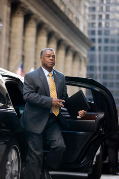 A Business Man Steps Out Of A Car Onto A Chicago Street.