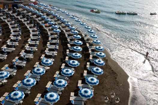 beach umbrellas and sun beds in the beach of atrani early in the morning, a man walking by