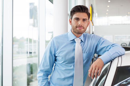 At the car dealer, Man leaning at new car