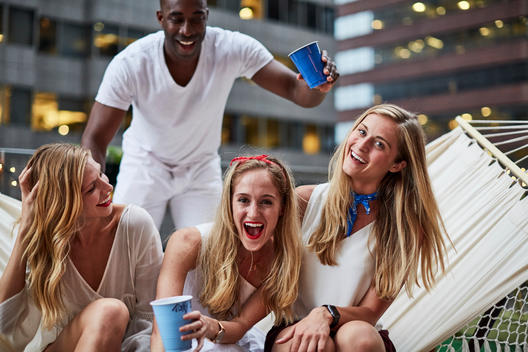 Women laughin on hammock at Fourth of July party