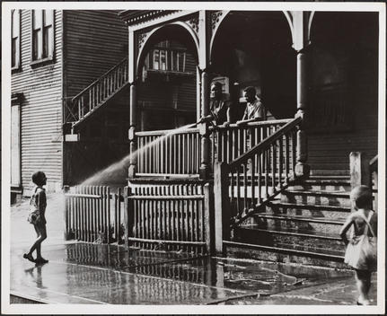 Children Spraying A Hose From A Porch