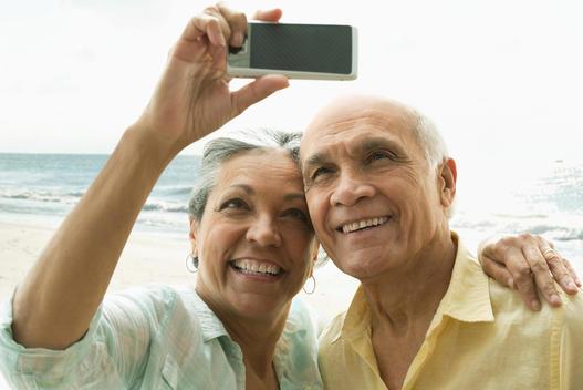 Older Hispanic couple taking selfie on beach