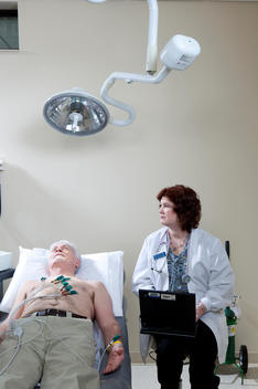An elderly male patient is lying on a hospital bed as a female nurse sits next to him