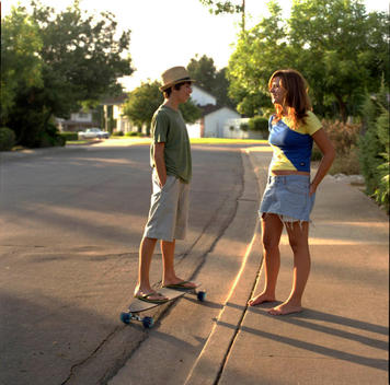 Two Teenagers With Skateboard On Suburban Street