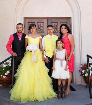 Hispanic family celebrating quinceanera outside Catholic church