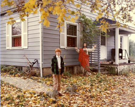 Boy In Front Of House With Statue Of Jesus