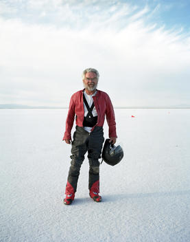 A Grey Haired Bearded Man Wearing A Leather Motorcycle Suit And Holding A Helmet Standing On The Salt Flats.