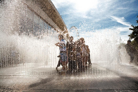 An Image Of A Group Of Young Children Standing In The Middle Of Water Fountain