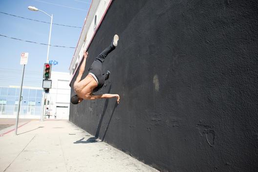 Man running up wall, demonstrating parkour