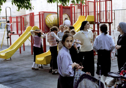 Young girls and their teachers in a playground.