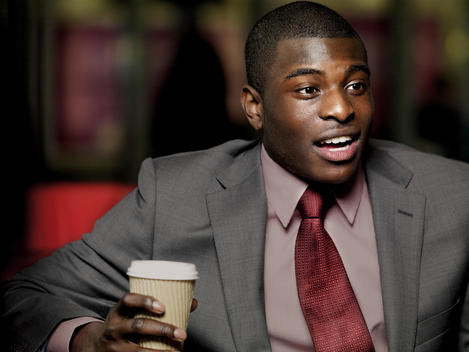 Man Of African Ethnicity, Dressed In Business Attire, Waiting With Coffee