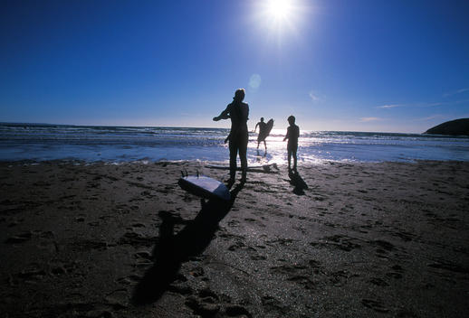 A Young Family - Husband, Wife And Son - Silhouetted By The Sun Go Surfing Together At Saunton Sands In Devon.