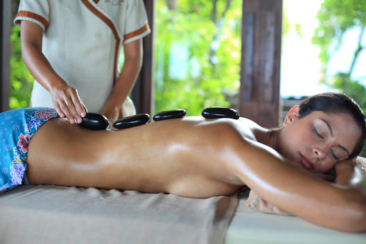 Woman receiving hot-stone massage therapy