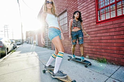 Women riding skateboards on city street