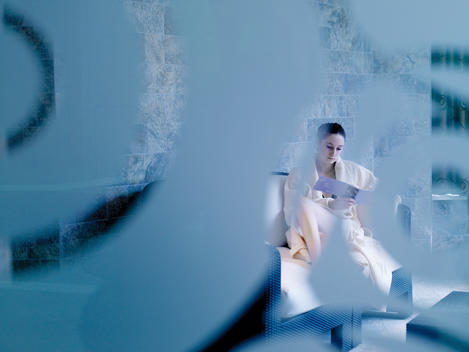 Woman Relaxing At A Spa And Choosing Her Next Treatment, Shot Through Glass